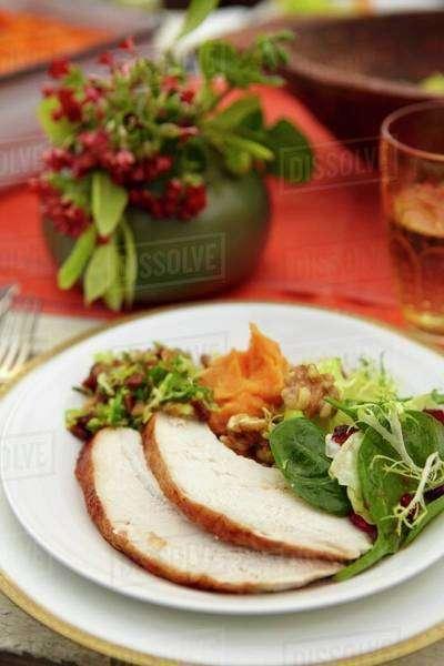 Thanksgiving Plate with Sliced Turkey, Salad and Sweet Potatoes; On a Set Table Royalty-free stock photo