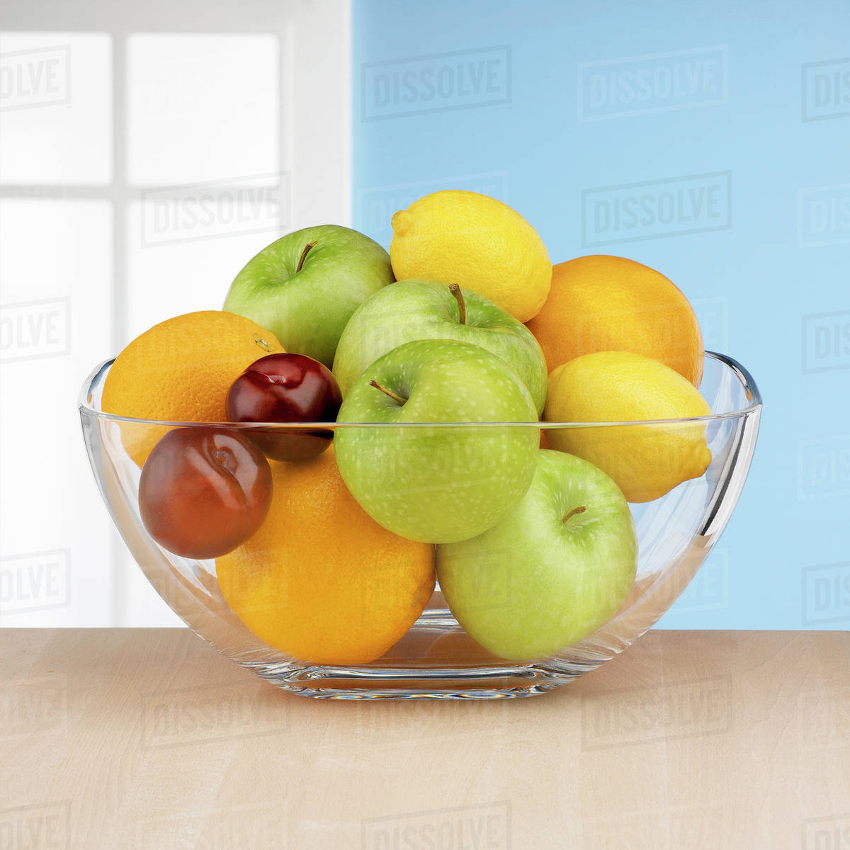 Fresh fruit in glass bowl in front of window Royalty-free stock photo
