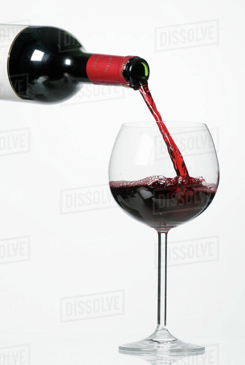 pouring red wine into glass from bottle stock photo dissolve