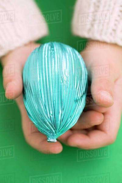 Child's hands holding Easter egg in blue foil Royalty-free stock photo