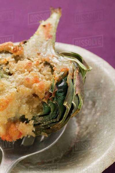 Stuffed artichoke with gratin topping on spoon, close-up Royalty-free stock photo