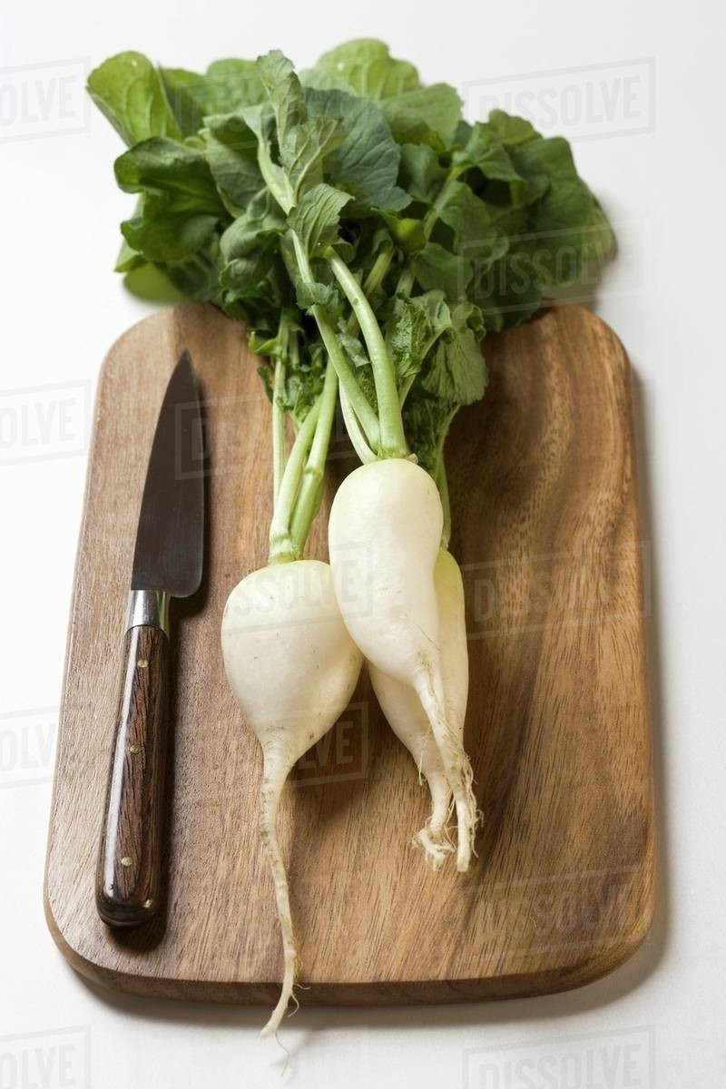 icicle radishes with leaves knife on chopping board stock photo