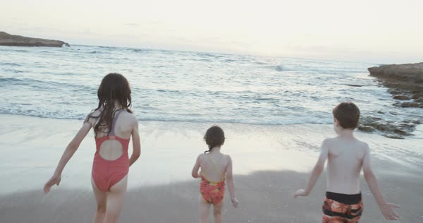 Three Kids Running Into The Water On Beach During Sunset Royalty Free Stock Video