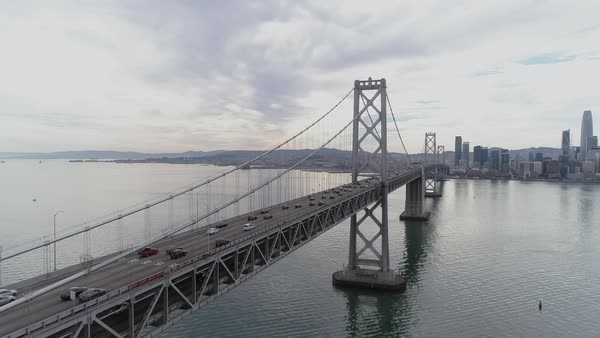 Aerial shot of traffic moving on San Francisco–Oakland Bay Bridge with city in background Royalty-free stock video
