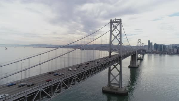 Aerial shot of vehicles moving on San Francisco–Oakland Bay Bridge with city in background Royalty-free stock video