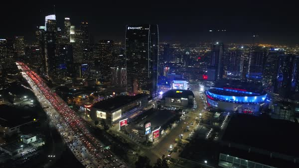 Aerial shot of traffic moving on street at night with Los Angeles skyscrapers Royalty-free stock video