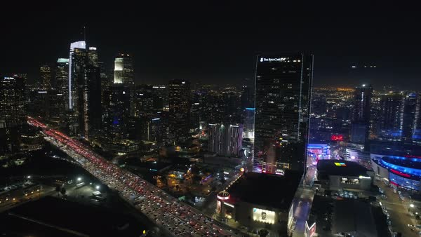 Aerial shot of traffic moving on street at night with Los Angeles city skyscrapers Royalty-free stock video