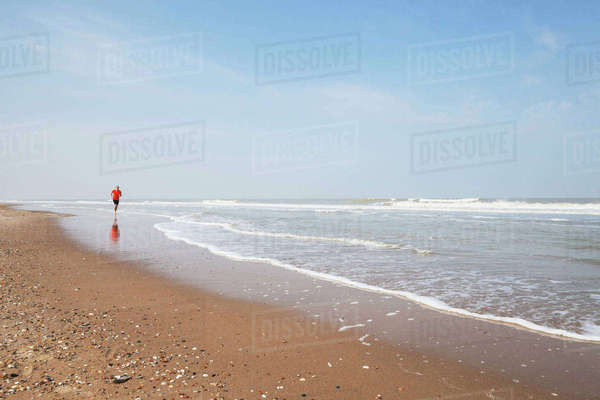 Belgium, Flanders, man jogging at seafront Rights-managed stock photo