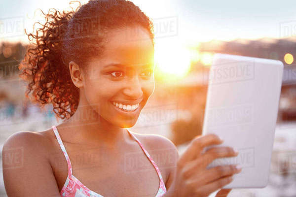 Happy young woman with digital tablet at sunset Rights-managed stock photo