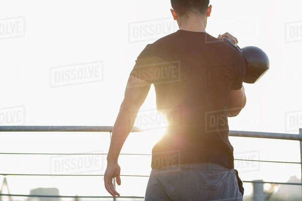Man training with kettlebell at backlight Rights-managed stock photo