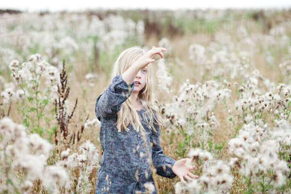 Girl standing in a field playing with seeds Rights-managed stock photo