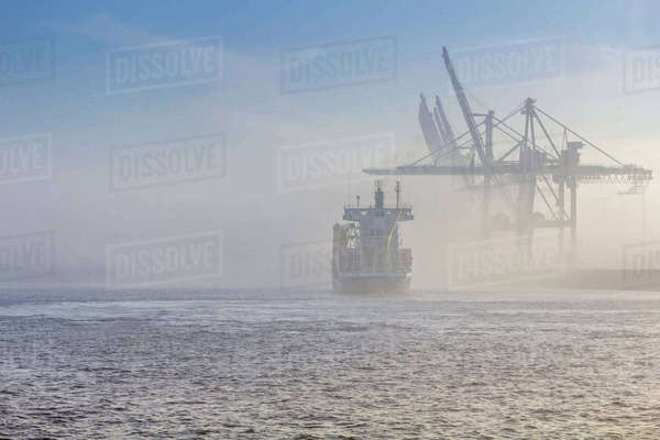 Germany, Hamburg, container ship disapears in the dense fog in the port of Hamburg Rights-managed stock photo