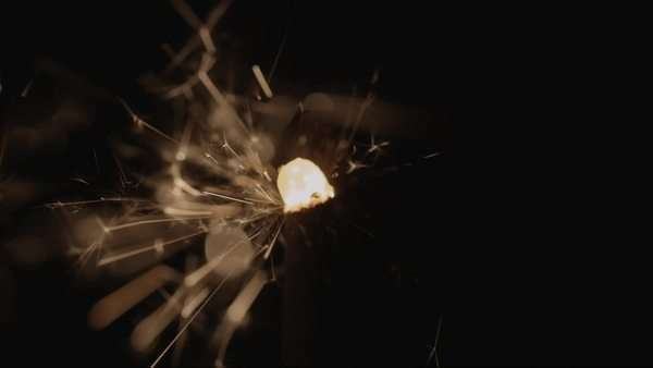 Static shot of a handheld firework that emits sparks on black background Royalty-free stock video