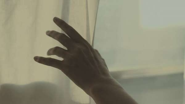 Handheld shot showing a hand touching a white window curtain Royalty-free stock video