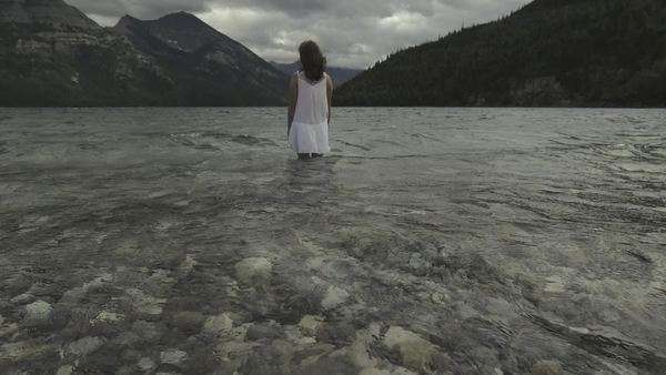 Handheld shot showing mountain scenery and the back of a woman standing in water Royalty-free stock video