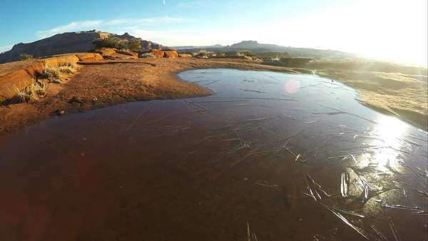 Panning view over frozen water towards the sun in the desert on the trail hiking to the Wave. Royalty-free stock video