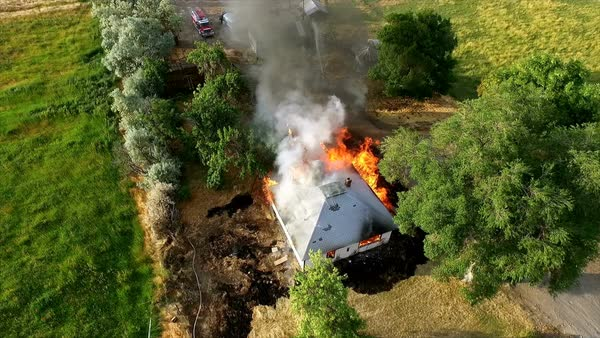 Aerial footage of house burning down during firemen training on a controlled burn. Royalty-free stock video