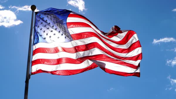 American Flag waving against a blue sky with sun glowing from behind. Royalty-free stock video
