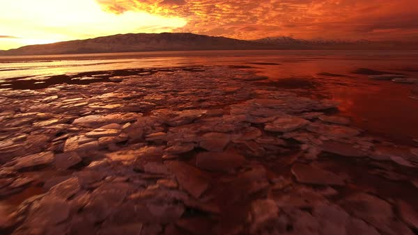 Flying low over frozen lake during colorful sunset on Utah Lake. Royalty-free stock video