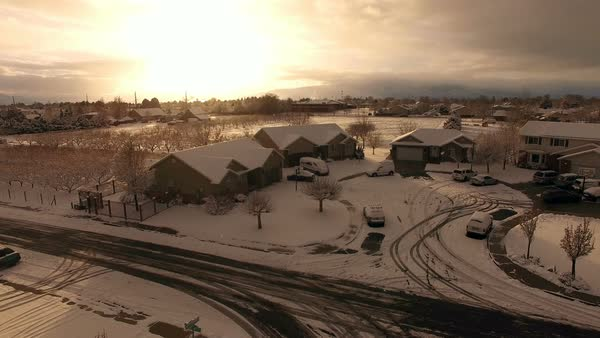 Flying over houses while snow is falling as the sun is setting on Christmas Day. Royalty-free stock video