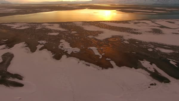 Flying backwards over frozen lake panning upwards to view colorful sky at sunset. Royalty-free stock video
