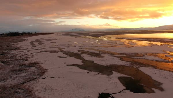 Aerial view of frozen landscape covered in snow during colorful sunset at Utah Lake. Royalty-free stock video