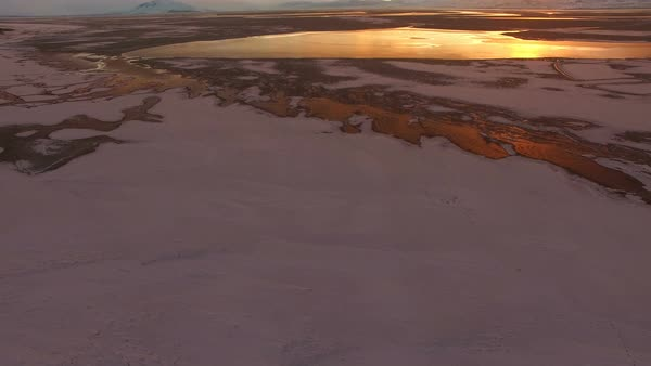 Flying over snow and ice covered landscape panning up towards the colorful sunset. Royalty-free stock video
