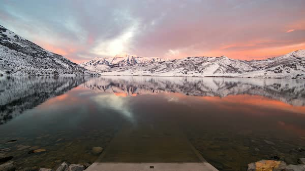 Timelapse of sunrise reflecting over lake surrounded by snow capped mountains at Deer Creek Reservoir Utah. Royalty-free stock video