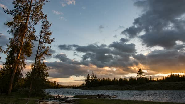 Timelapse after the sun has set over forest along river in Yellowstone moving on slider Royalty-free stock video