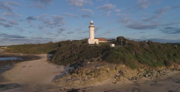Norah Head lighthouse aerial view with cloudy sky and sandy rocky beach in New South Wales Australia Royalty-free stock video