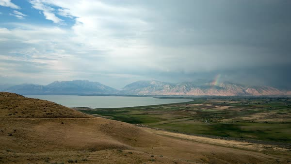 Time lapse over grassy hills towards lake and mountains in Utah County Royalty-free stock video