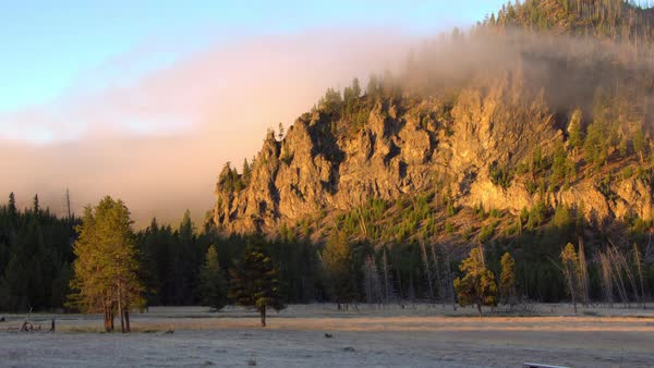 Fog rolling past hillside lit up in the morning in Yellowstone. Royalty-free stock video
