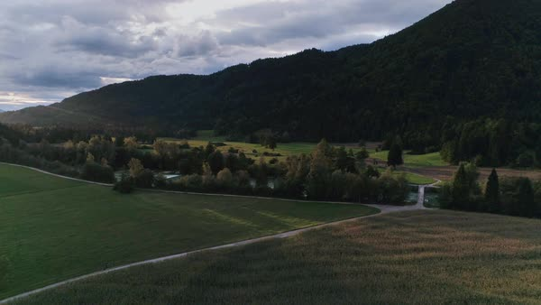 Aerial view flying over the landscape in Lepena Valley from open fields towards the foliage along the Soca River. Royalty-free stock video