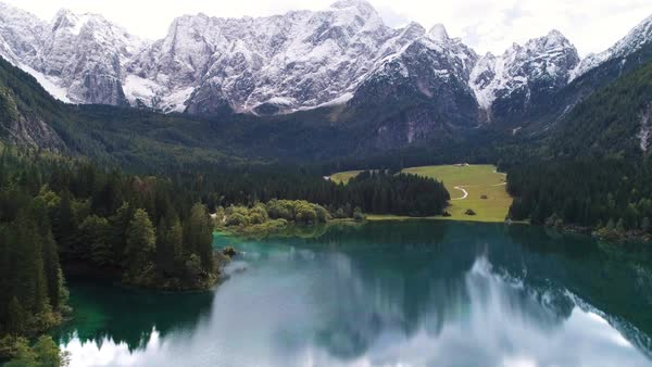 Aerial view above colorful Lake Fusine flying towards the Julain Alps viewing Mangart covered in snow towering through the green forest. Royalty-free stock video