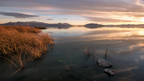 Panning timelapse turning towards the sunset over Utah Lake as the sky lights up and reflects in the mirror surface of the lake. Royalty-free stock video