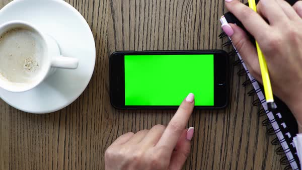 Hand holding smart phone with coffee on wood desk. Green screen and can be add your texts Royalty-free stock video