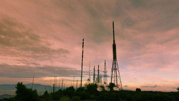 A wide view of the cell and broadcast telecommunication towers and antennas site at the the top of the mountain. Timelapse at dusk in warm colours. Royalty-free stock video