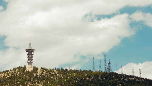 Communications towers and radars on top of a mountain timelapse with cloudy sky background. Royalty-free stock video