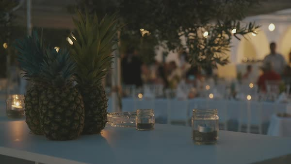 Pineapples and decorations at open air summer bar restaurant at dusk Royalty-free stock video