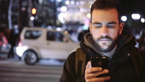 A cheerful young man is browsing his cellphone on a busy urban street at night. Royalty-free stock video