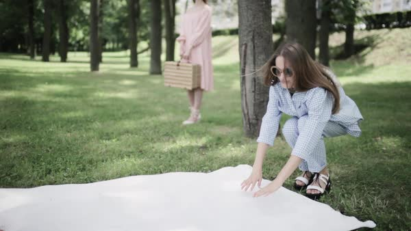 Medium wide shot of a woman laying down a white blanket in a park Royalty-free stock video