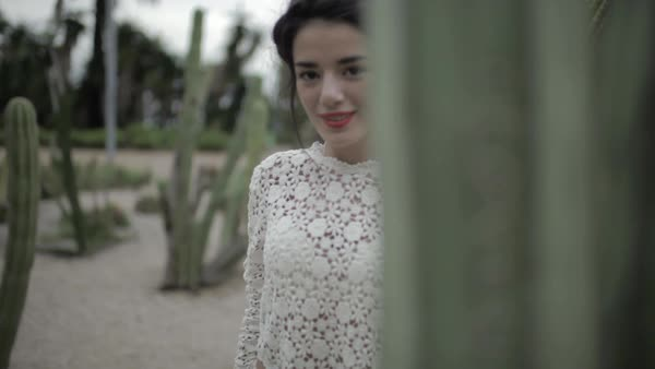 Medium shot of a woman posing behind a cactus Royalty-free stock video