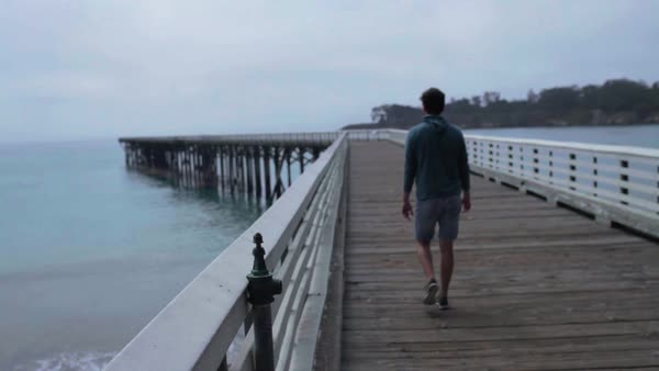 Hand-held shot of a man walking on a pier Royalty-free stock video