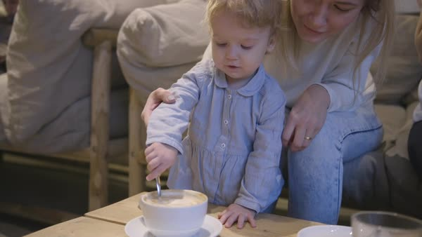 Hand-held shot of a mother helping her toddler stir a cup Royalty-free stock video