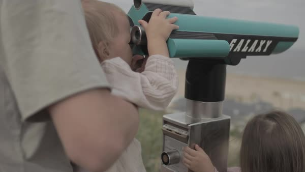 Hand-held shot of a father and a toddler looking through an outdoor telescope Royalty-free stock video