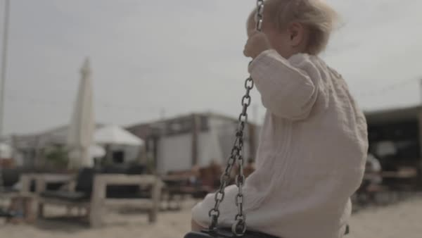 Hand-held shot of a toddler spinning on a swing Royalty-free stock video