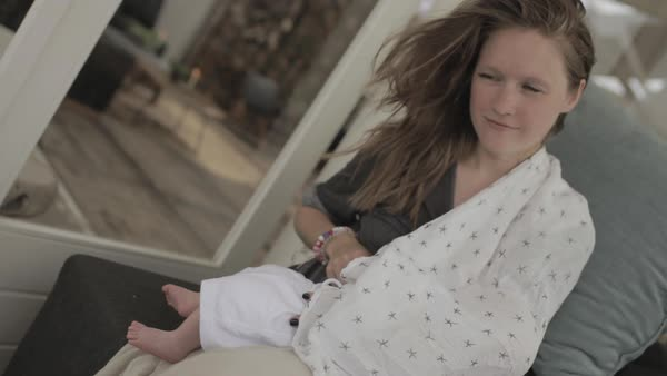 Hand-held shot of a young mother breastfeeding her baby in her lap Royalty-free stock video