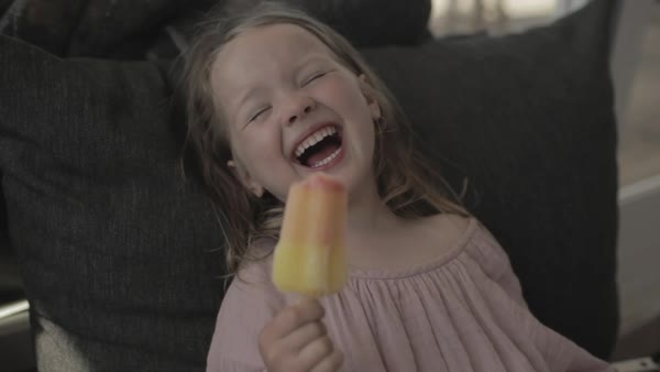 Hand-held shot of a girl laughing while eating ice cream Royalty-free stock video