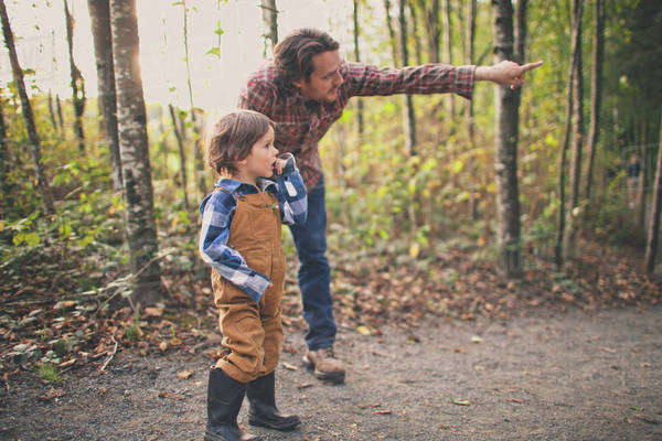 A father points to a birds nest to show his young son. Royalty-free stock photo