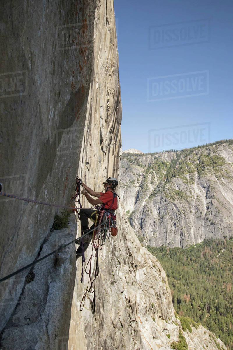 man climbing on rocky mountain of el capitan, yosemite national park